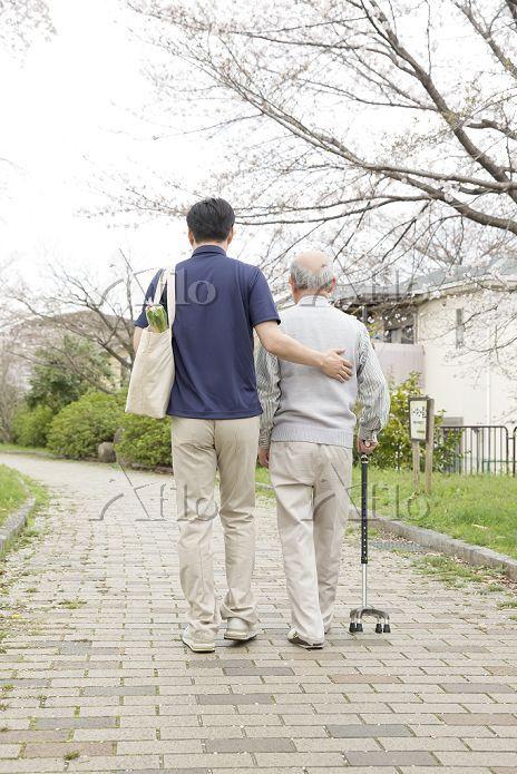 杖のシニアと歩く買い物袋を提げた後姿の男性ヘルパー