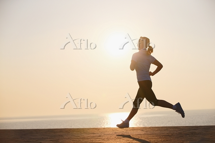 太陽とジョギングする女性