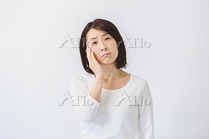 顔を押さえる40代日本人女性