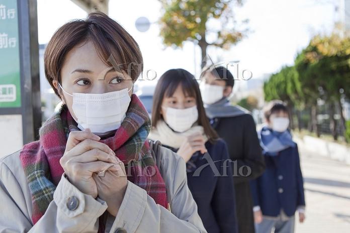 マスクをしてバス停に並ぶ人々