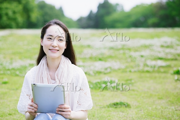 芝生の上でiPadを使う女性