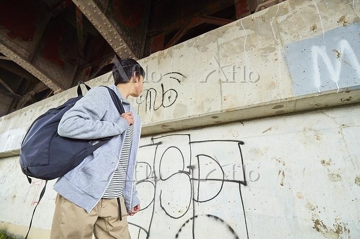 壁の落書きを見る日本人中学生