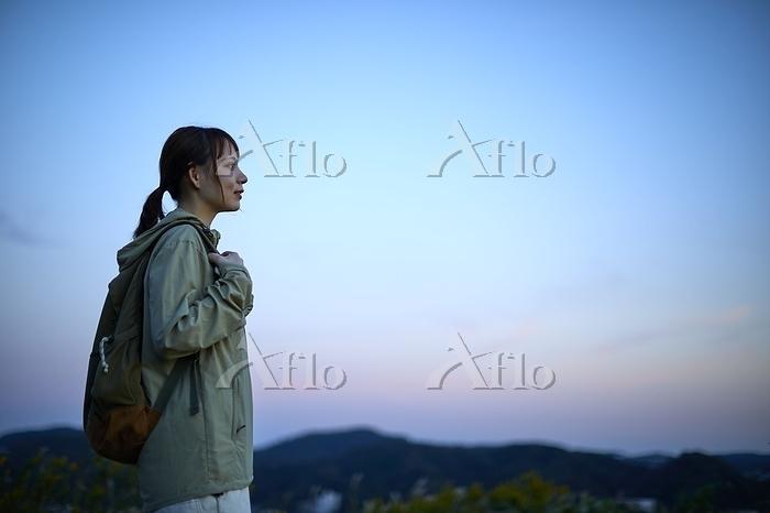 遠くを眺める女性登山者