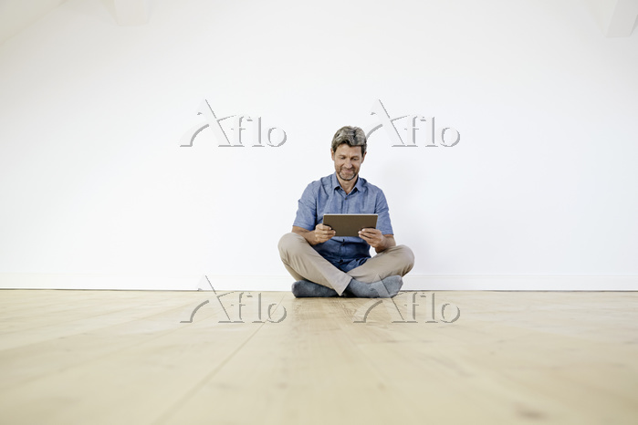 Mature man sitting on ground i・・・