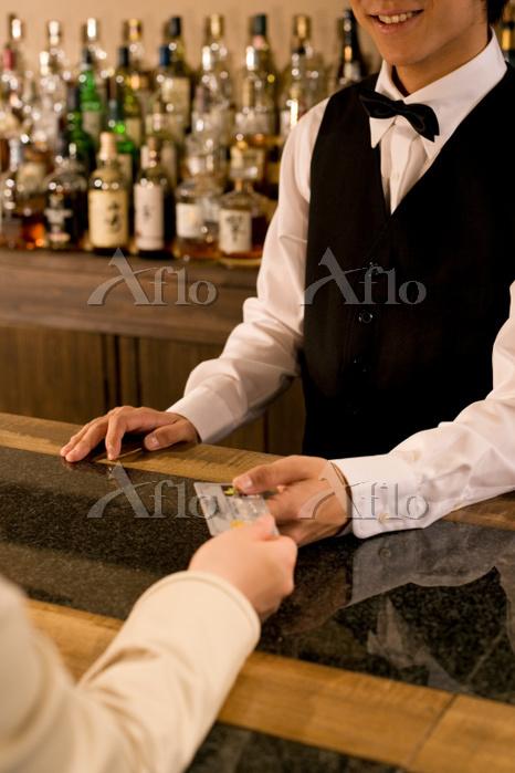 バーテンダーにグレジットカードを渡す女性の手元