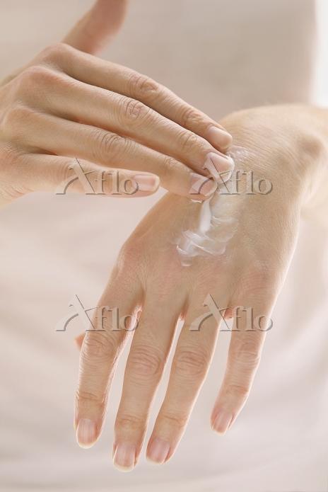 手にハンドクリームを塗る
