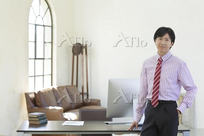 明るく広いオフィスで働く日本人ビジネスマン