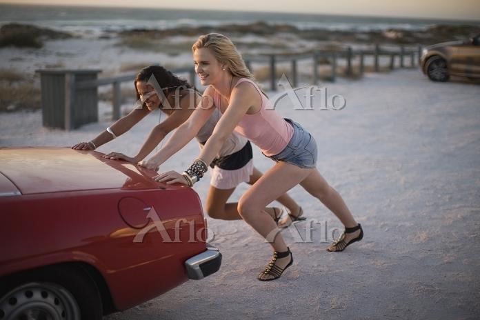 Girls pushing their broken car