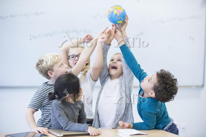 Happy pupils holding globe tog・・・
