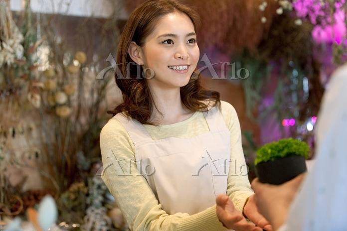 花屋で働く日本人女性店員と客