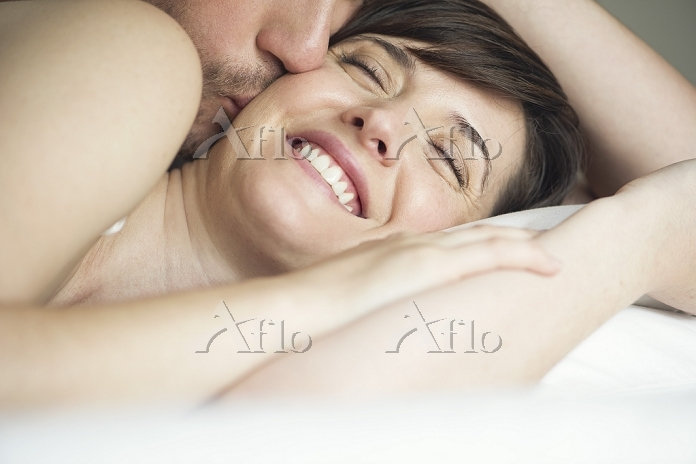 Couple cuddling in bed, husban・・・