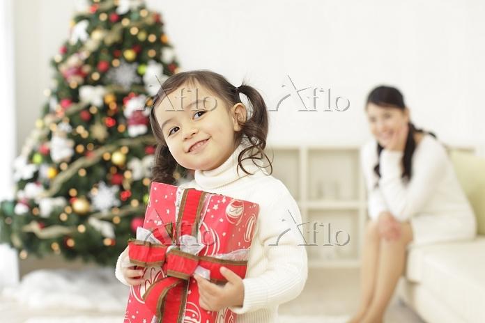 クリスマスプレゼントを持つ女の子と見守るお母さん