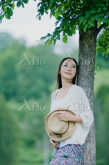 木にもたれる日本人女性