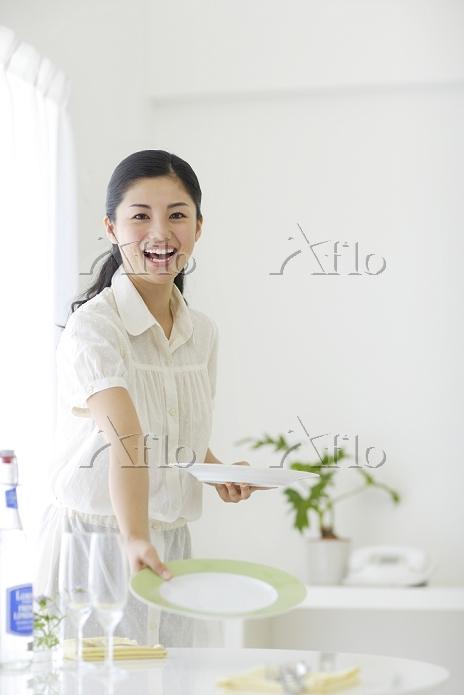 皿を並べて朝食の準備をする若い女
