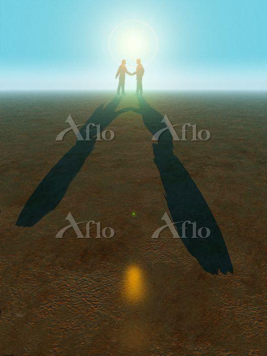 逆光の草原で握手するビジネスマン
