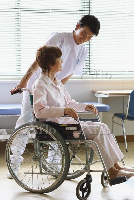 シニアのケアをする若い男性看護師