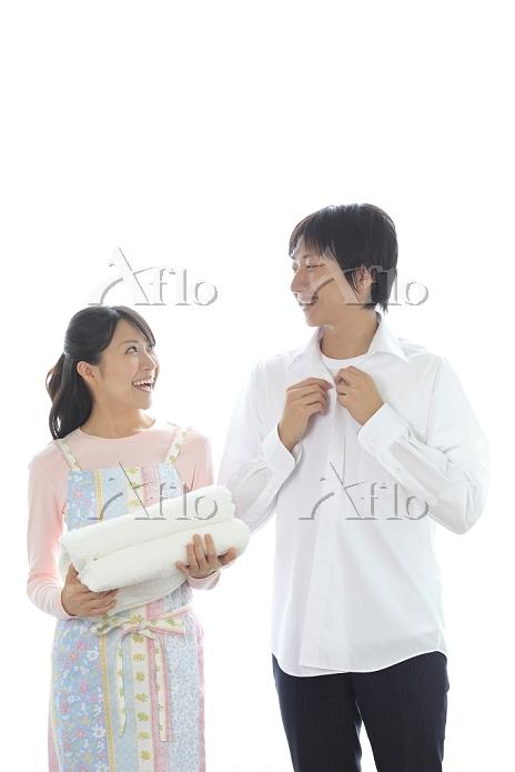 洗濯したシャツを着る夫とタオルを持つ妻