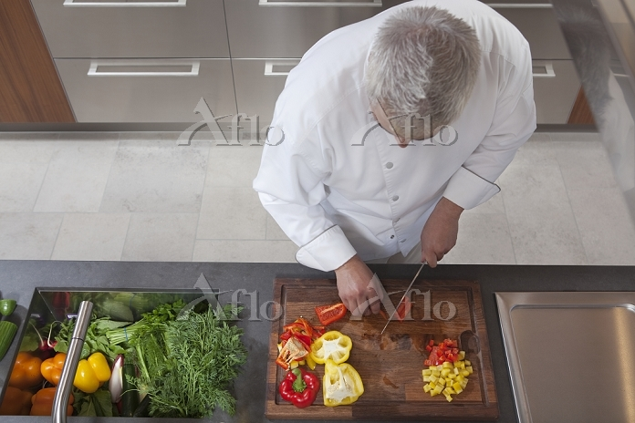 Mid- adult chef dices peppers ・・・