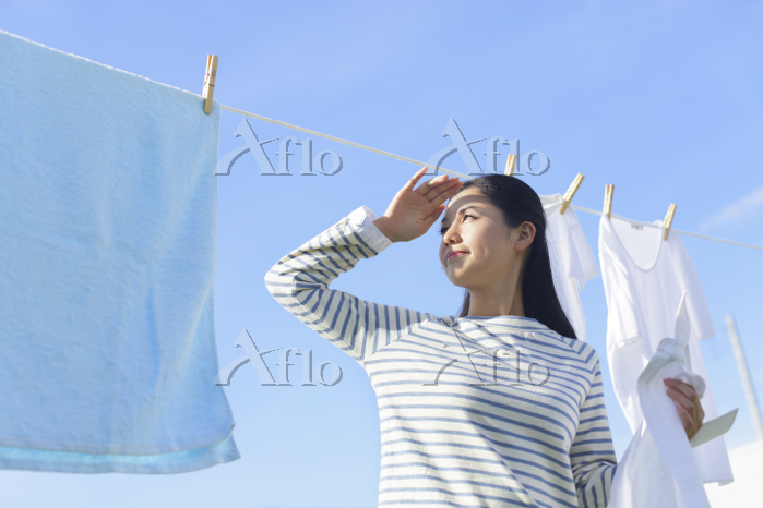 眩しい太陽の下で洗濯物を干す主婦