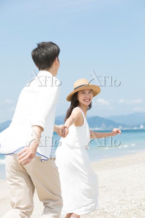 海辺で手をつないでいるカップル