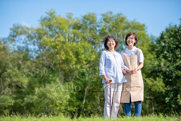 シニア女性の歩行を介助する介護士