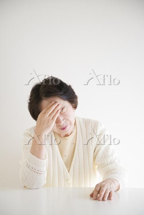 額に手をやる年配の女性