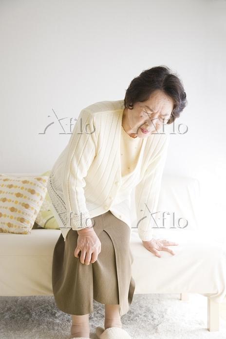 膝を押さえて立ち上がる年配の日本人女性