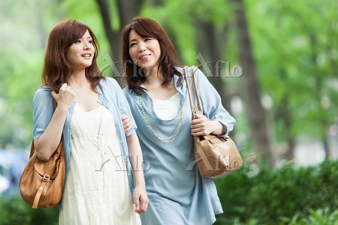 腕を組む笑顔の母と娘