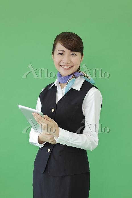 タブレットを持つ制服を着た若い女性