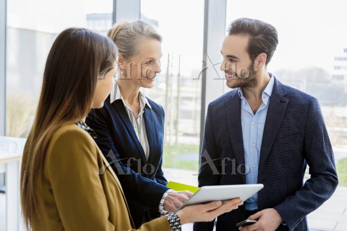 ミーティングタブレットを見て話すビジネスチーム