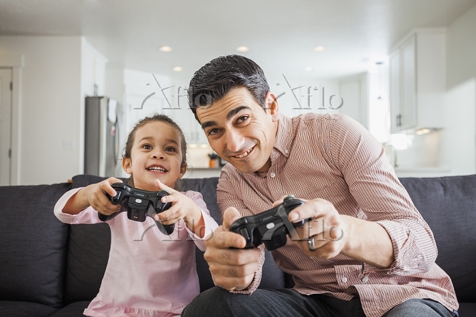 TVゲームをする娘とお父さん