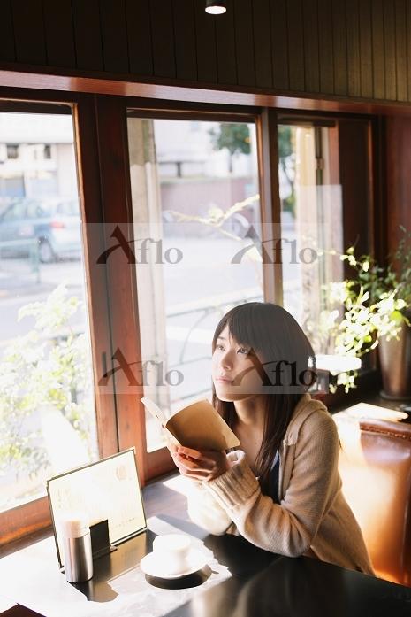 喫茶店で本を読む日本人女性