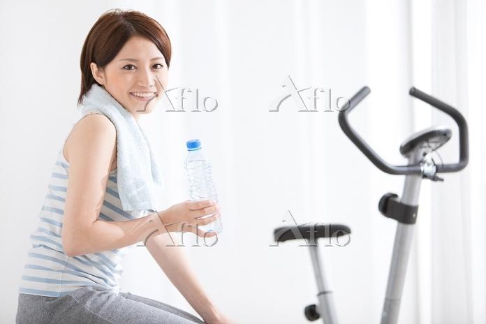 ミネラルウォーターを持って座る女性