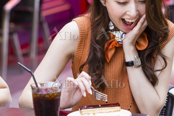 オープンカフェでケーキを食べる日本人女性