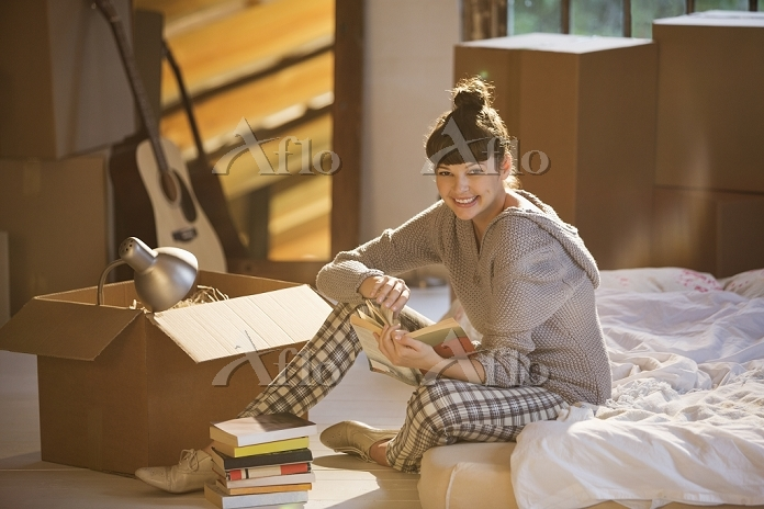 Woman holding book in bed