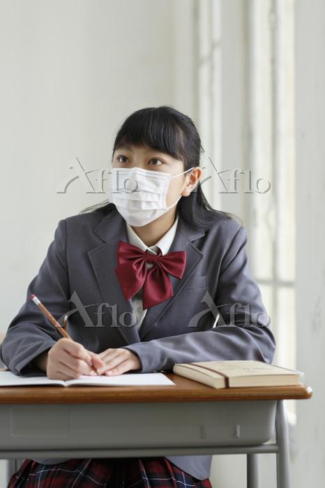 マスクをして授業を受ける女子高生