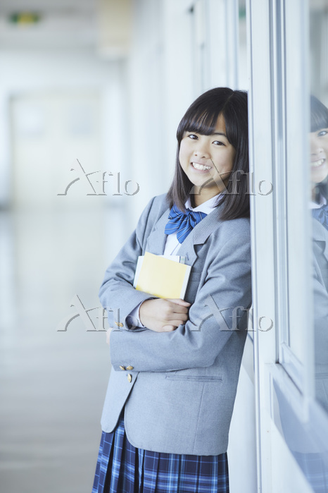教室の窓にもたれかかる女子中学生