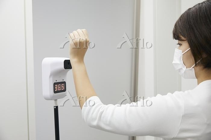 非接触体温計で検温する女性