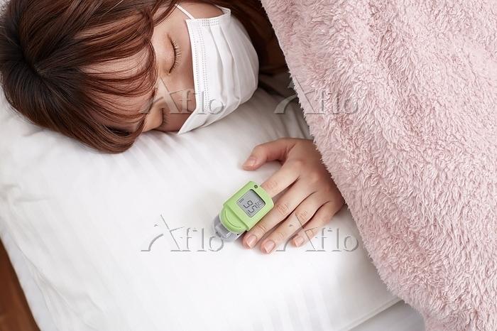 パルスオキシメーターで血中酸素濃度をはかる日本人女性