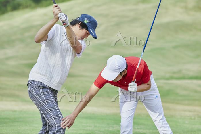 ゴルフのレッスンを受ける日本人男性