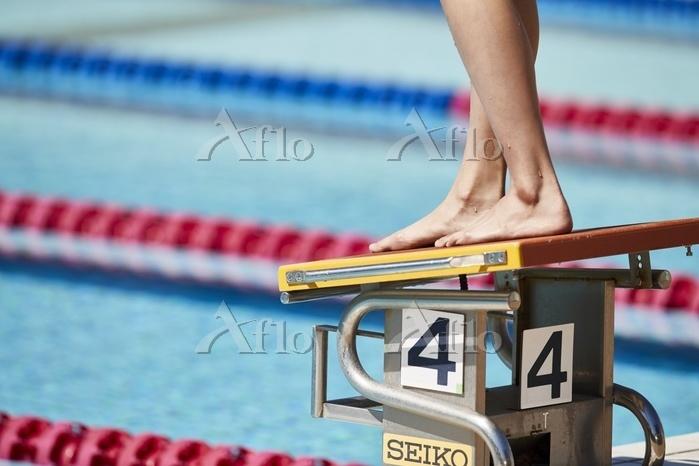 飛び込み台に立つ女子水泳選手の足元