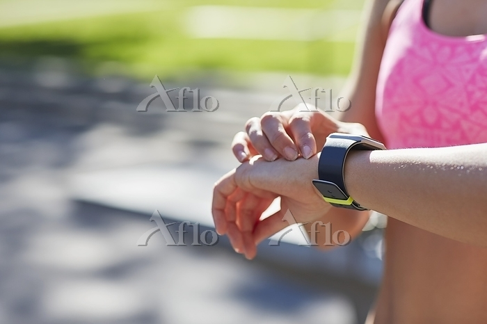 Woman wearing sports watch che・・・