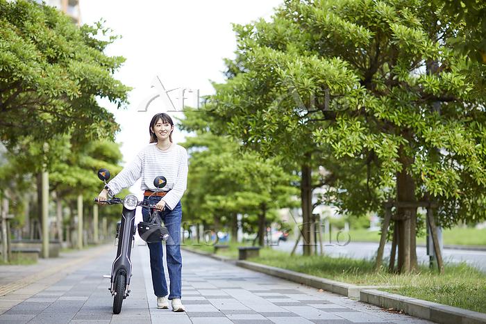 電動バイクを押して歩く女性