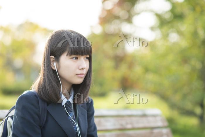 ベンチで音楽を聴く女子高生