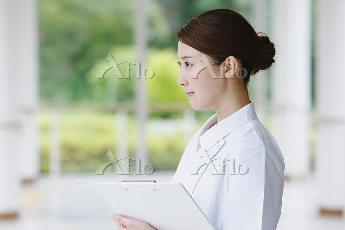 廊下にいる若い日本人女性看護師