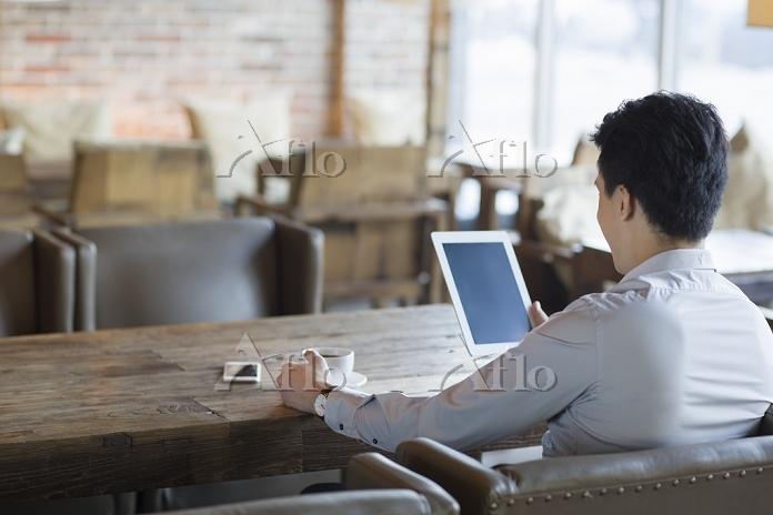 カフェでiPadを見る中国人ビジネスマン