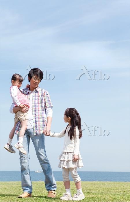 芝生を歩く父と娘