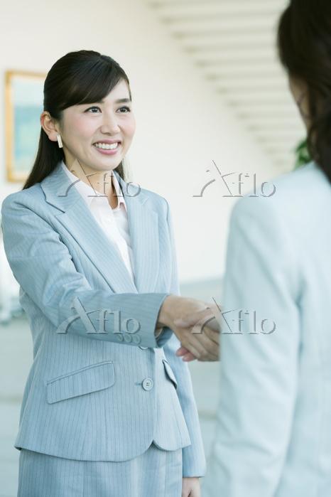 握手をする日本人ビジネスウーマン