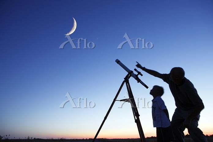 天体望遠鏡で三日月を見る親子