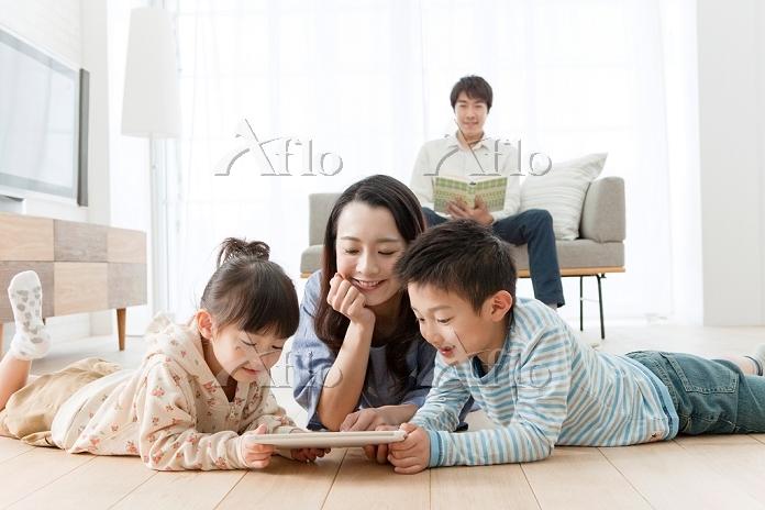 タブレットを見る兄と妹と母親
